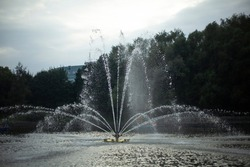 Fountain on the water. Stream of water beat upwards. City pond decoration. Lake in the city.