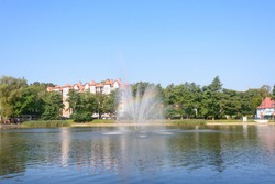 Fountain on water with rainbow splashing. Selective focus, blur.