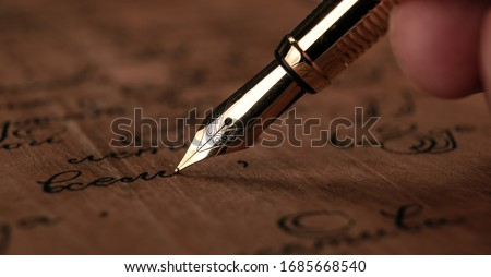 fountain pen in the hand with paper with ink text on the wooden desk closeup Stock photo ©