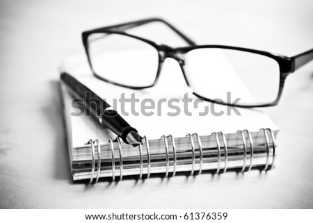 Fountain pen notebook and glasses in composition in black and white