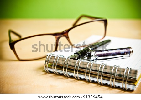 Fountain pen notebook and glasses in composition in color
