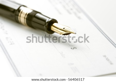 Fountain pen on blank check. Focus on tip of pen and dollar sign symbol