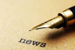 Fountain pen on news text