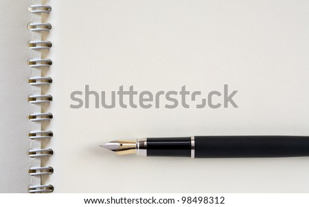 Fountain pen on open spiral notebook. Good background with free space