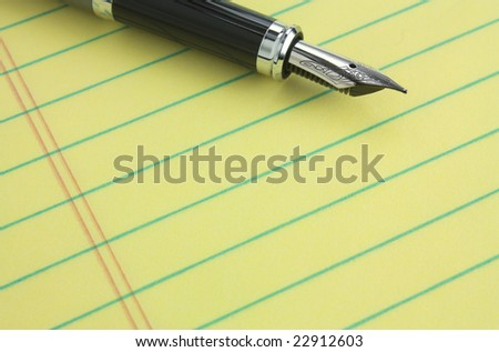 Fountain pen on yellow legal pad of paper - add your business message