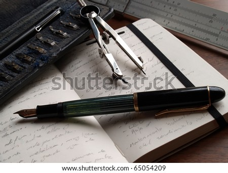 fountain pen over notebook and classic engineer tools