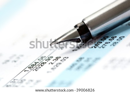 Fountain pen over page of financial figures.  Very shallow depth of field, focus on pen tip.