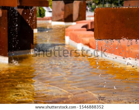 Fountain with brick edges with metal structures that make beautiful water drop curtains #1546888352