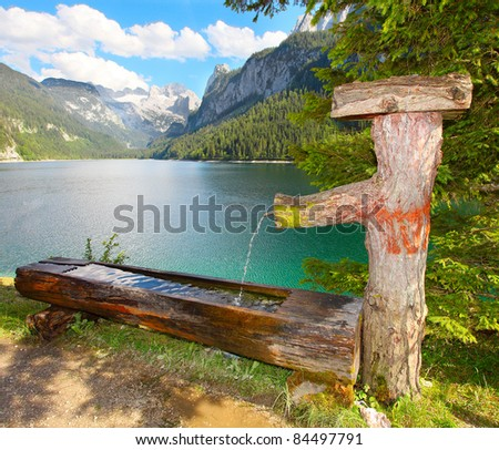 Fountain with drinking water over a Vorderer Gosausee alpine mountain lake in Salzkammergut, Austria, Europe.