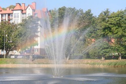 Fountain with rainbow in sunlight. Selective focus, blur.