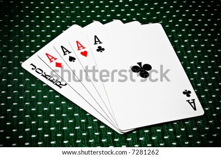 Four aces and a joker fanned out against a unique patterned tabletop.