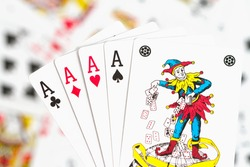 four aces and a joker on the background of scattered cards