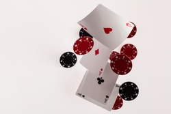 Four aces and casino poker chips falling on white background.  Room in frame for copy.