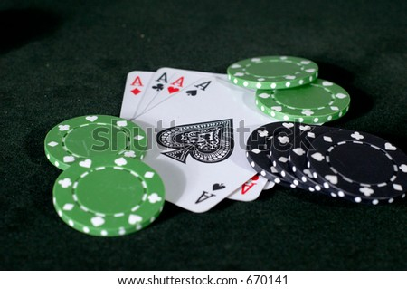 four Aces and  king, with black and green chips scattered.
