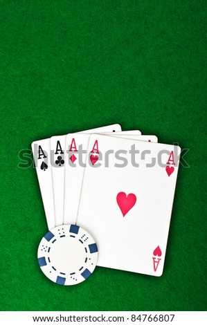 four aces and poker chips on a green felt