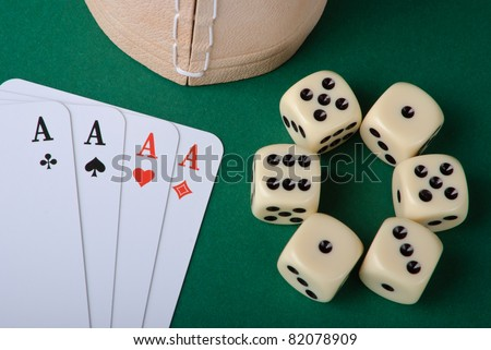Four aces and six dices with cup on green background