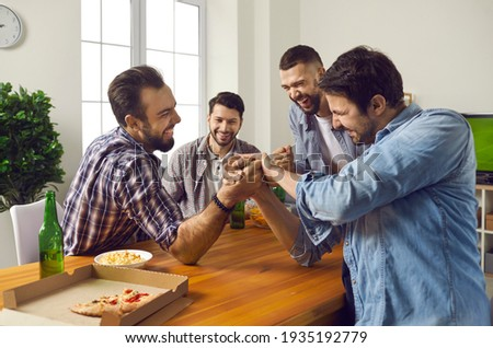 Four adult friends have fun together on the weekend. Cheerful company of male friends at home drinking beer and competing in arm wrestling. Concept of friendly competition, strength and men's leisure. ストックフォト ©