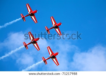 four airplanes in formation on airshow
