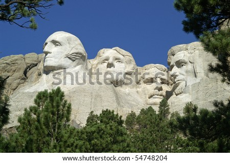 Four American Presidents framed by bushes and ponderosa pine trees at Mount Rushmore National Memorial, South Dakota
