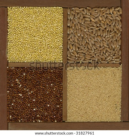 four ancient cereal grains - millet, spelt, amaranth, red quinoa in a wooden box or drawer with dividers