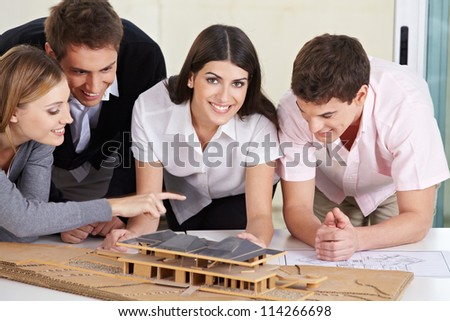 Four architects discussing a 3D house draft in their office