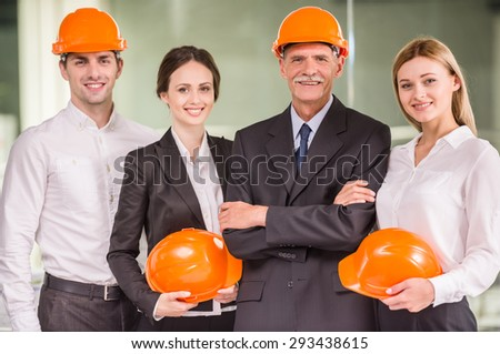 Four architects standing together at office and posing to camera. Team work concept.