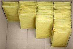 Four ascending rows of bubble envelopes inside a big cardboard box.