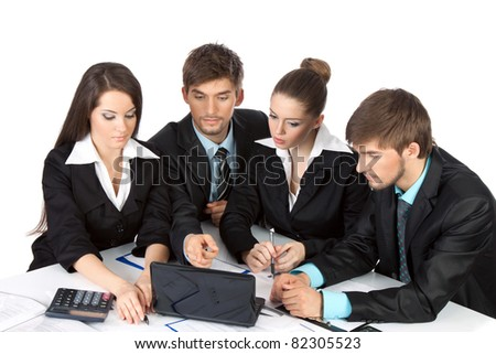 four attractive positive young business people in elegant suits sitting at desk in front of a laptop computer with papers, document point finger working in team together Isolated over white background