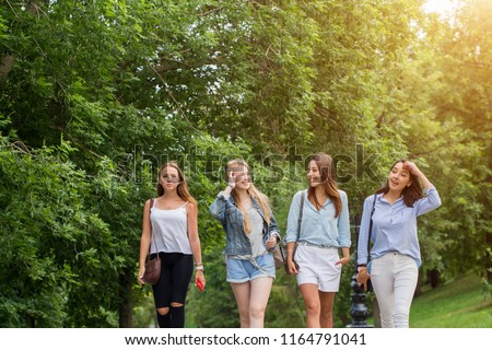Four attractive young friends women talking and walking together on walkway with trees #1164791041