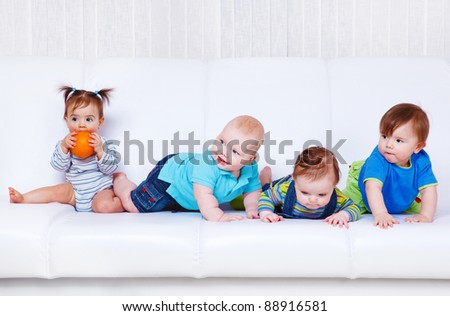 Four baby friends sit and lie on  white sofa