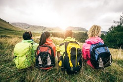 Four backpackers looking at sunset over the mountains - Hikers talking and relaxing after an excursion in the nature - Friends enjoying winter holiday