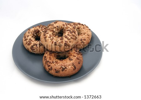 Four bagels with sunflower seeds on gray plate - Isolated