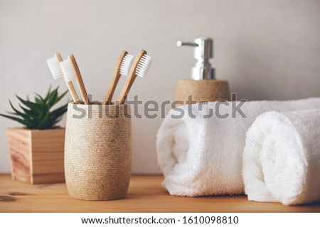 Four bamboo toothbrushes in a cup and white towels Foto stock ©