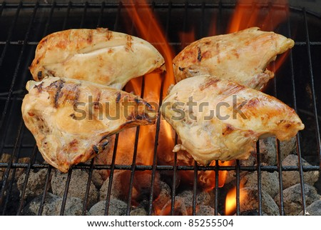 four barbecue chicken breasts with flames