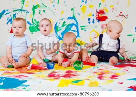 Four barefoot babies playing with paints