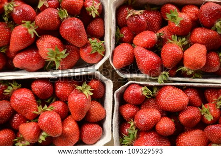 Four Baskets Of Fresh Strawberries In A Street Market