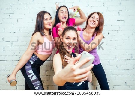 four beautiful and young women taking pictures on the phone in s