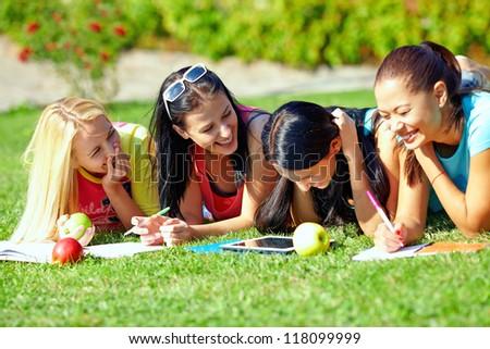 four beautiful girl having fun outdoors on green lawn