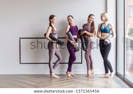 Four beautiful slim positive young girls fitness models are preparing for joint training and rejoice at the meeting. The concept of sports lifestyle and like-minded people. Yoga concept