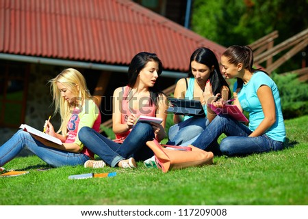 four beautiful students girls prepare for the exam on green lawn
