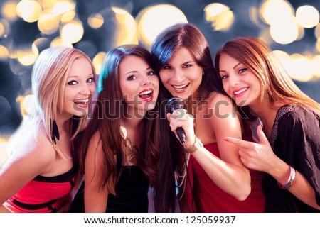 Four beautiful stylish girls singing karaoke at the club