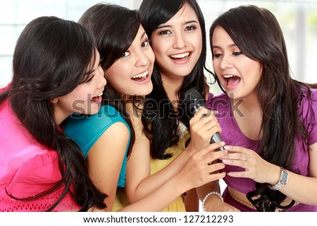 Four beautiful stylish woman singing karaoke together