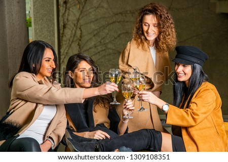 Four beautiful young cheerful women looking happy and playful while drinking Champagne and cheers. Just having fun and exploring the city #1309108351