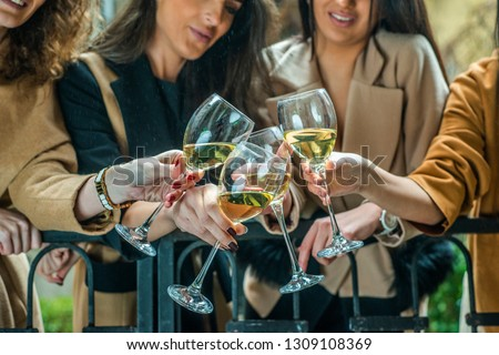 Four beautiful young cheerful women looking happy and playful while drinking Champagne and cheers. Just having fun and exploring the city #1309108369