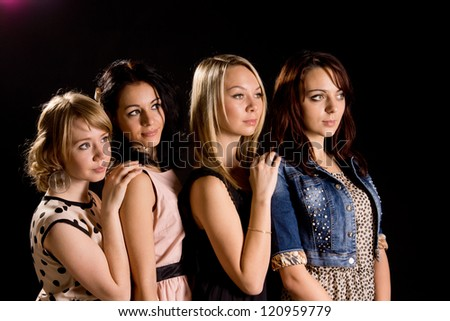 Four beautiful young female friends posing behind each other in a row against a dark background