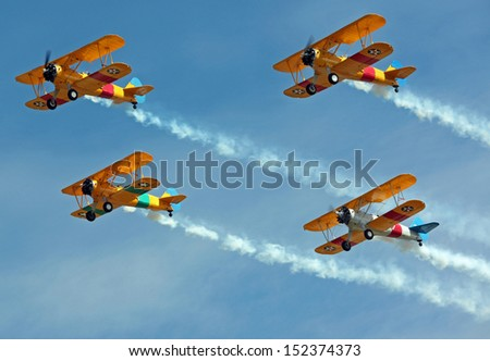 four biplanes flying in...