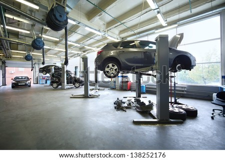 Four black cars in garage with special equipment prepared for repair.