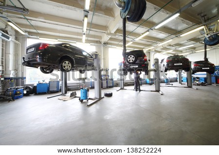 Four black cars on lifts in small service station and two men repair one car.
