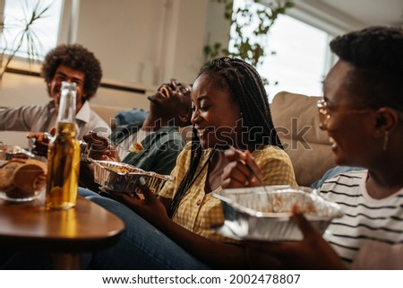Four black friends used their free time hanging together and just have fun. They are eating takeout food while sitting on the floor in the living room Foto stock ©