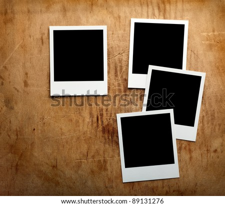 Four blank instant photo frames on old wooden background.